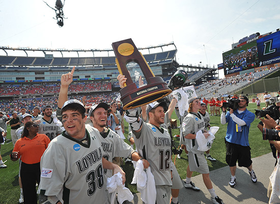 Graduate student and attackman Eric Lusby holds the NCAA National Championship trophy up, surrounded by his teammates.