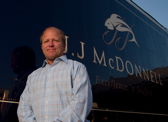 George McManus III standing by a JJ McDonnell truck, smiling.
