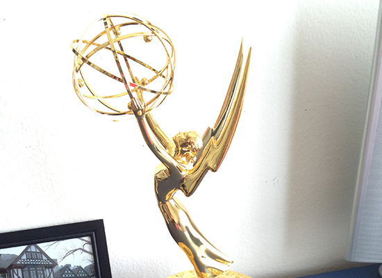 Suzanne's Emmy Award next to a black and white photo of Loyola's humanities manor.
