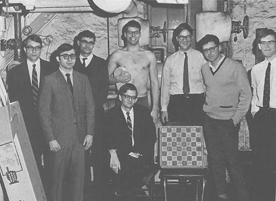 Black and white photo of Tom Clancy in the Student Center basement with his chess club mates.