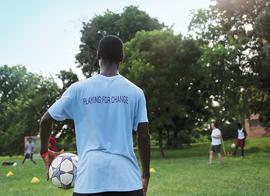 Young student stands holding a soccer ball. The back of his shirt reads