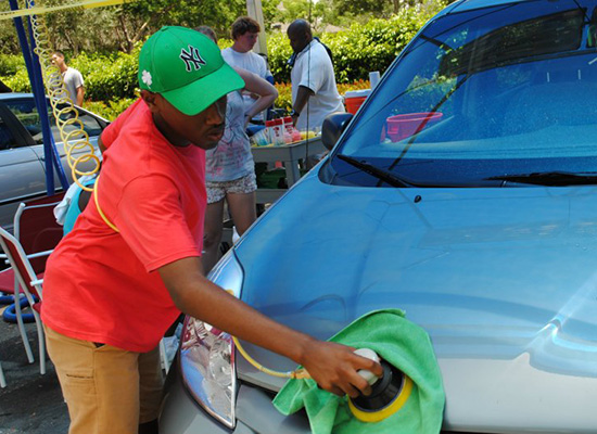 Young man polishes the hood of a car.