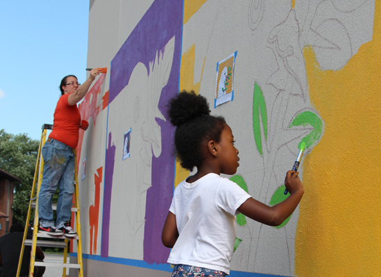 Young girl paints bright green leaves on outdoor mural.
