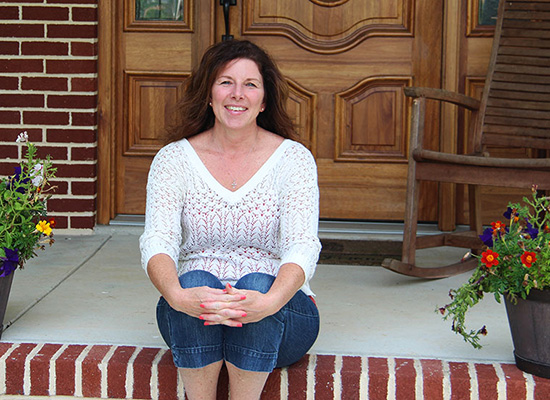 Beth sits on a brick step in front of her home, smiling.