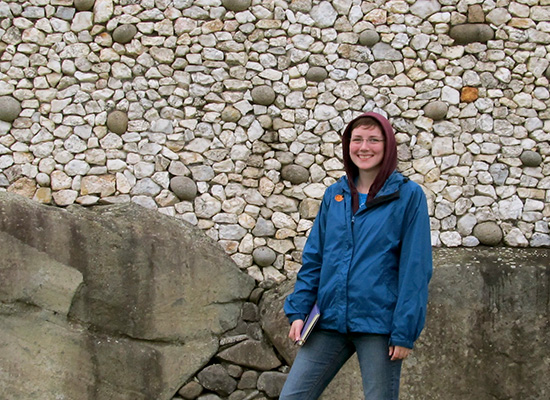 Rory in front of an old, stone wall, smiles at the camera.
