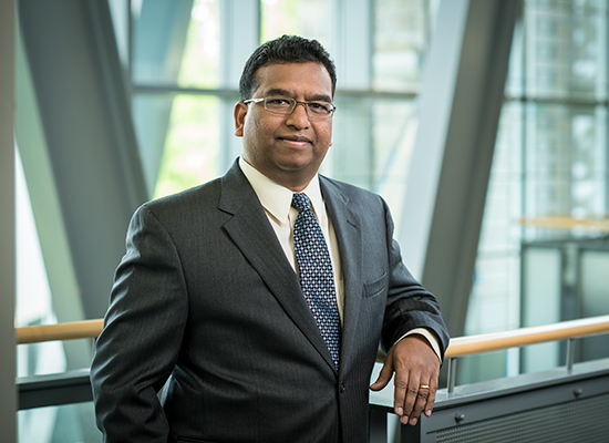 Frank D'Souza leans on railing inside the Sellinger School of Business.