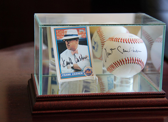 Card and signed baseball of Frank Cashen in a glass display box.