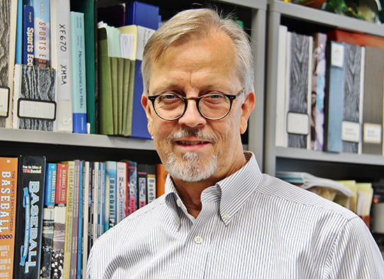 Photo of Steve Walters Ph.D., in office with bookshelves behind him.