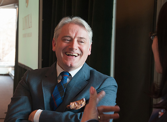 Graham McAleer crossing his arms and smiling as he speaks to event attendee.