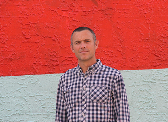 Photo of Tom Butler in front of a red and white, duo color wall.