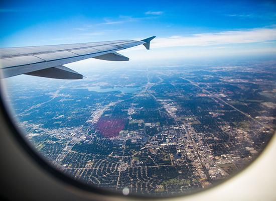 Plane window overlooking aircraft wing, blue horizon, and the earth below.