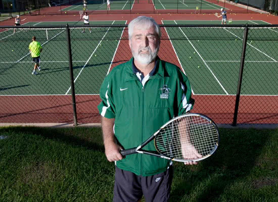 Rick McClure holding a tennis racket in front of tennis courts