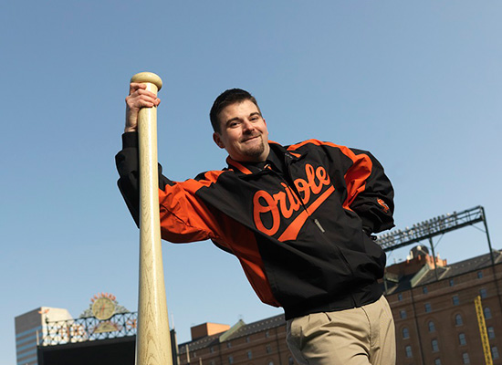Steve Butz leaning on large baseball bat and wearing his Orioles jacket.