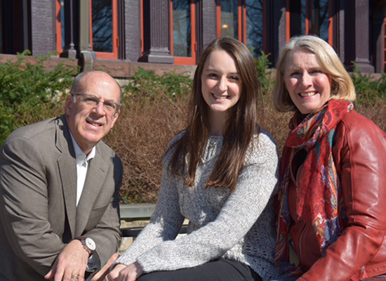 Meredith sitting with her parents in front of the humanities manor.