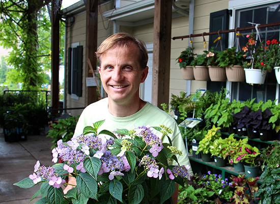 Peter Bieneman surrounded by pots of various plants and flowers.