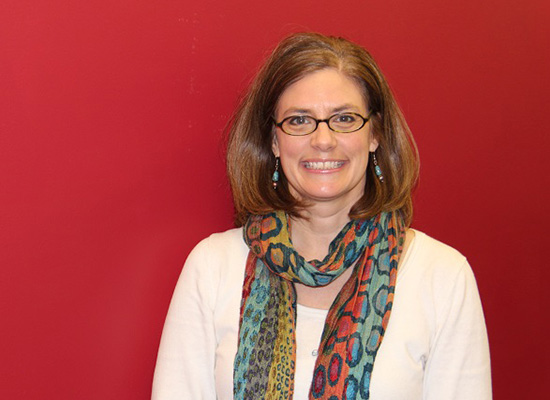 Beth Kotchick, Ph.D., smiles in photo with red background.