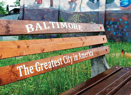 Baltimore City bench with mural in the background.