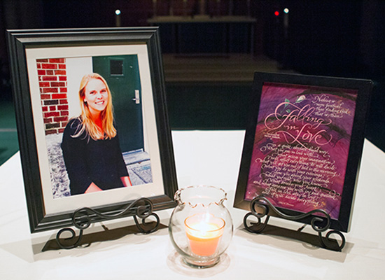 Memorial photo of Colleen with candle lit in front of frame.