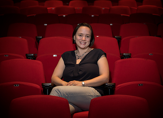 Natka sits among red theatre seats.