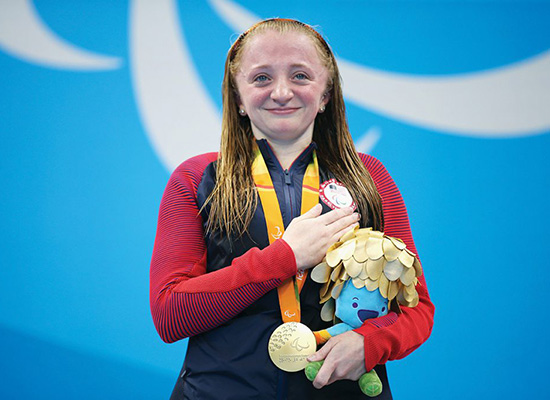 McKenzie Coan, '18, celebrates on the podium at the medal ceremony for the women's 50-meter freestyle.