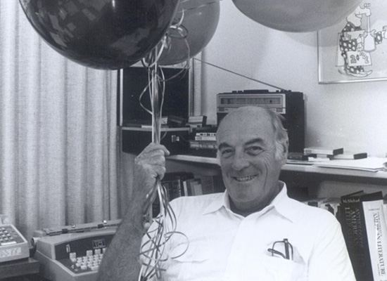 Charles Hands sitting in a chair holding a bundle of helium balloons.