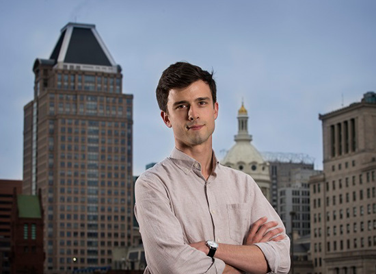 Photo of Patrick Diamond crossing his arms with Baltimore's skyline in the background.