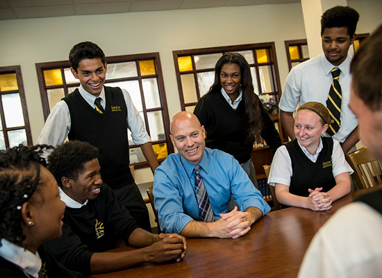 Bill Heiser sits at a desk, surrounded by students.