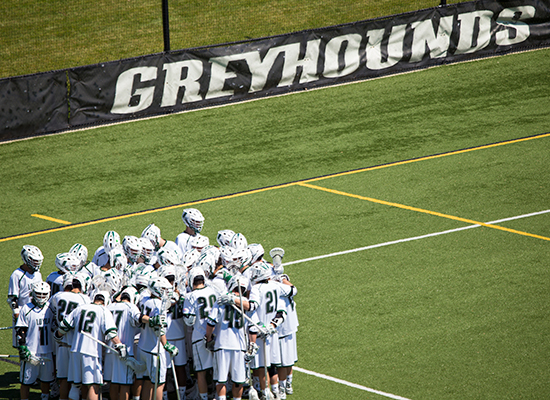 Greyhounds lacrosse team huddles together on the field.