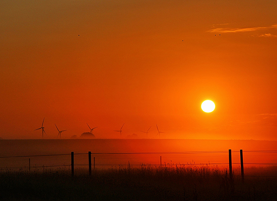 Red sunset over a field with wind turbines on the hazy horizon.