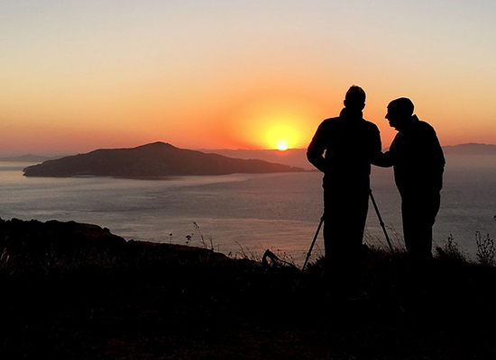 Silhouettes of an elderly and middle aged man, overlooking the sunset across the sea.