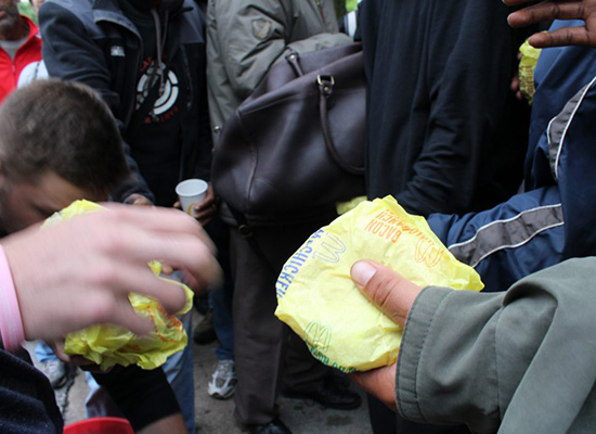 Amidst people, a hand holds a McDonalds' sandwich.