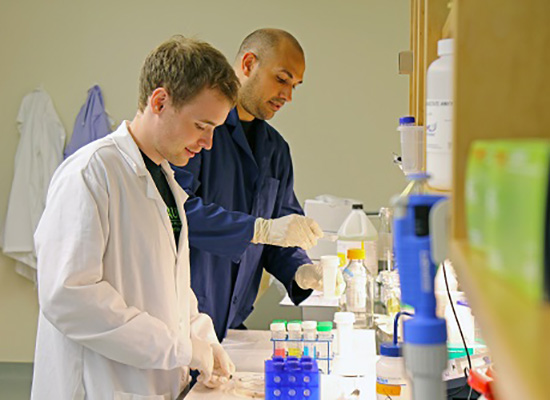 Student and supervisor handle lab materials.