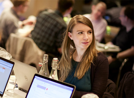 Brittany Beckert surrounded by peers at a function with laptops open.