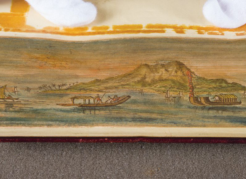 Fore-edge painting of boats on the water, surrounding a small, mountainous island.