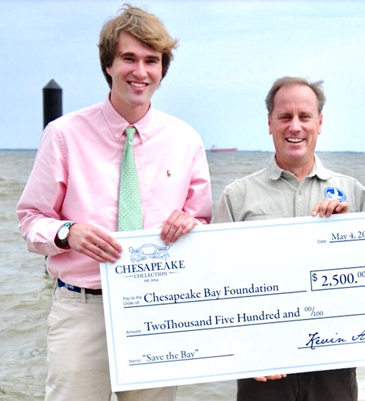 Matt stands by the water, holding a large check.