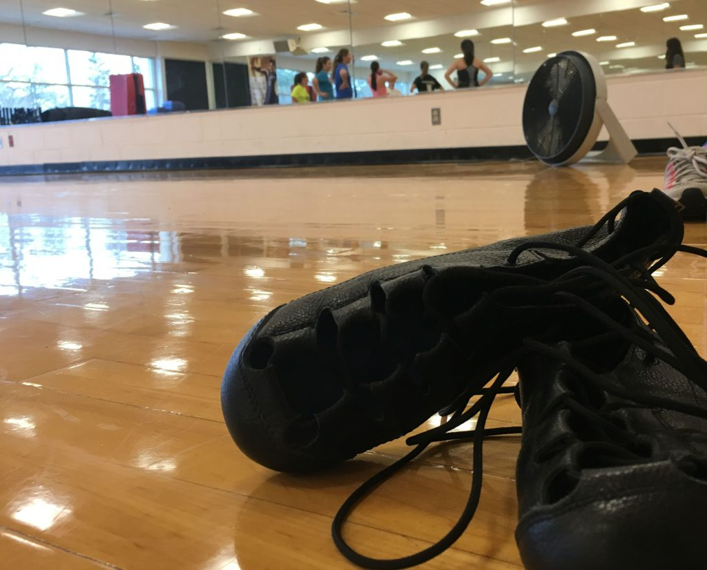 Black Irish dancing shoes on a wooden dance floor