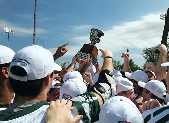 Loyola athletes gather in cheer and lift their trophy.