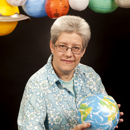 Inge Heyer photo portrait with air-filled planetary models above her.