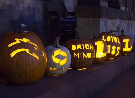 Carved pumpkins on the humanities manor porch with Loyola symbols and logos glowing with candlelight.