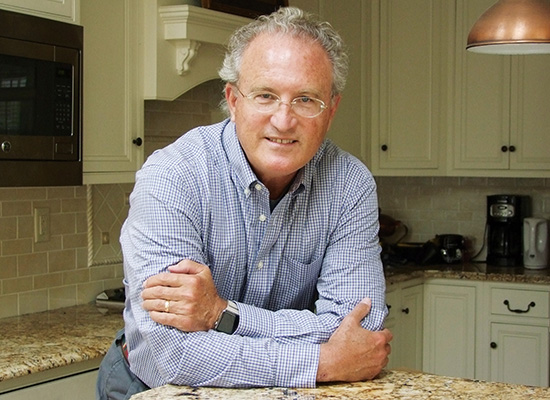 Photo of Mark Bowden leaning on kitchen counter with his arms crossed.