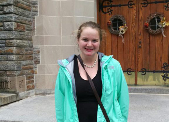 Photo of Caitlin in front of alumni chapel entrance.