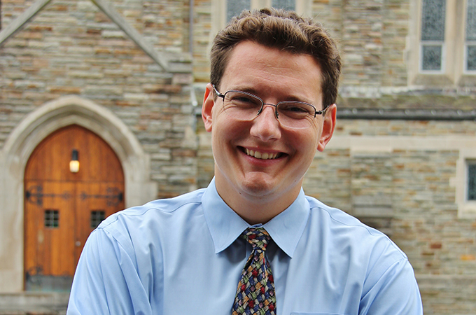 Krahel crosses his arms and smiles in front of Alumni chapel.