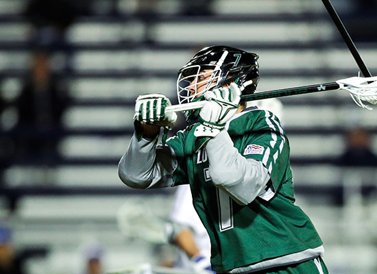 Pat Spencer runs in full lacrosse gear wearing the renowned Loyola green.