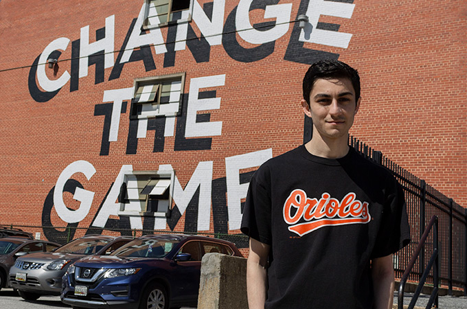 Andrew standing in front of a red brick wall with the words Change the Game written on it