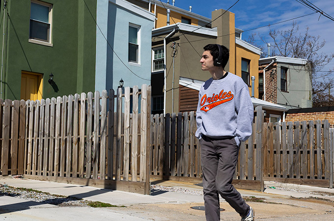 Andrewing walking through a neighborhood with rowhomes in Baltimore