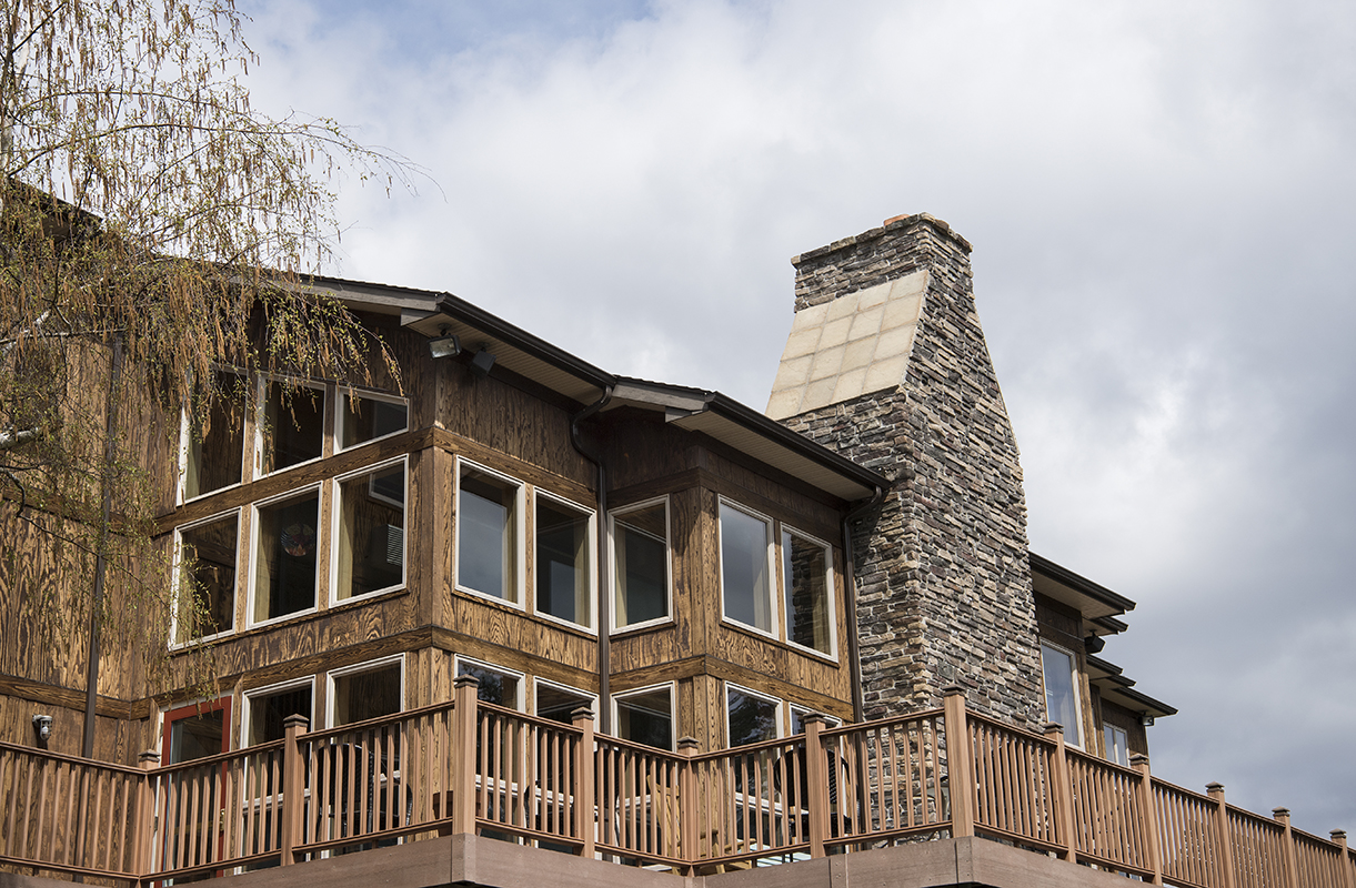 Retreat house with big stone chimney and great wooden porch.