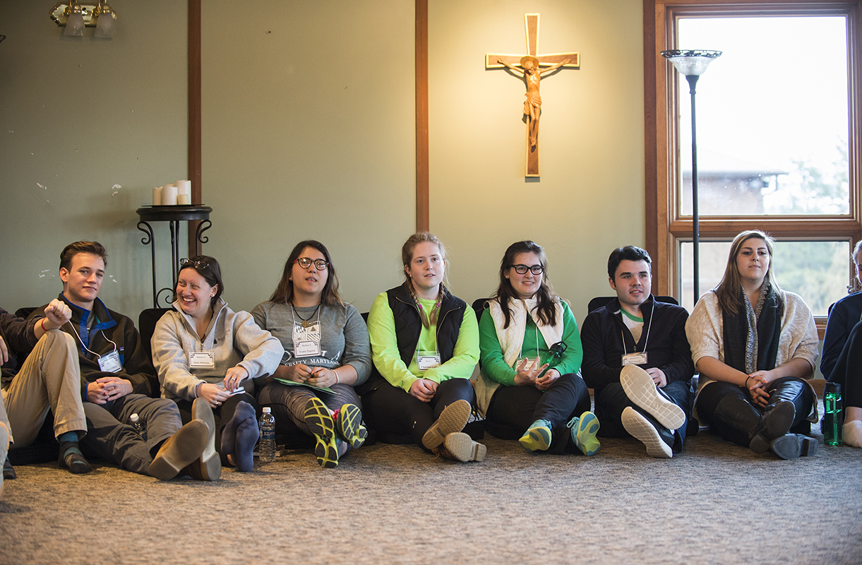Students sit against the wall with a crucifix above them.