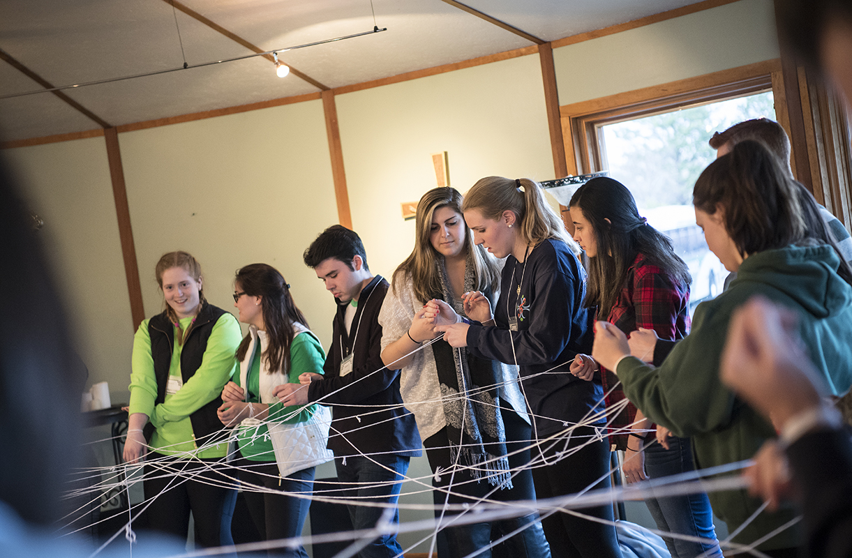 Students hold a web of strings.