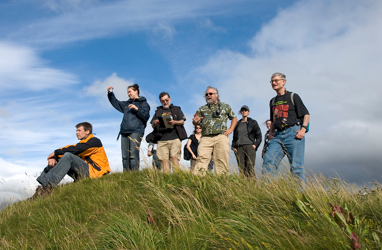 Kelly Devries and others standing atop a green grassy hill