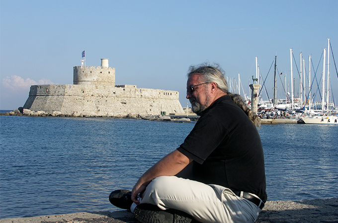 Kelly Devries sits on a stone wall overlooking a harbor, with a stone fort in the background